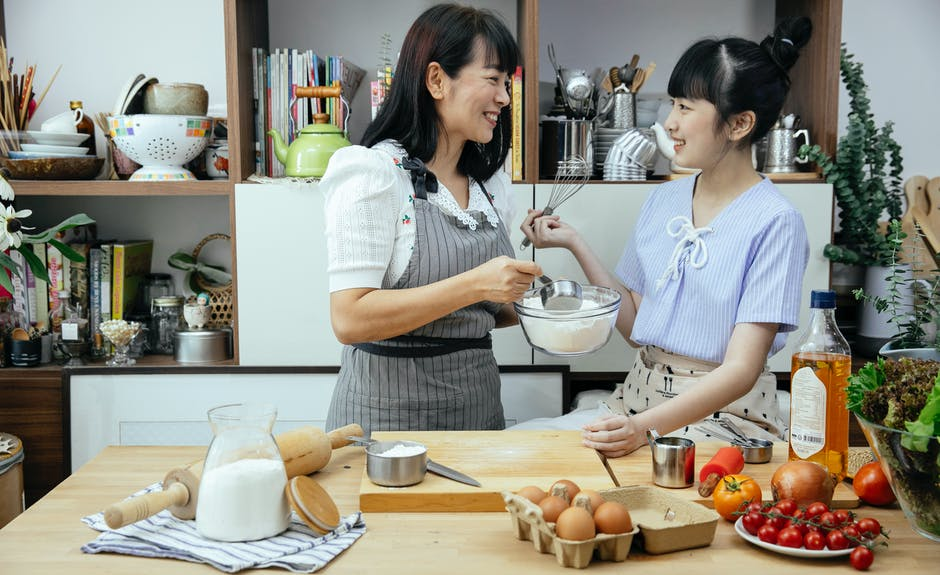 A woman standing in a kitchen preparing food
